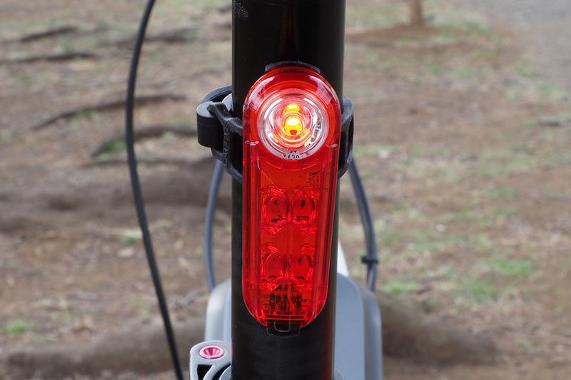 """こちらはテールライトの「SYNC KINETIC」(<a href=""""https://www.cateye.com/jp/products/safety_lights/TL-NW100K/"""" class=""""strong bn"""" target=""""_blank"""">公式ページ</a>)。シートポスト(サドル下のパイプ)に装着していて、曇天下の点灯イメージです。後方から見ると鋭いような赤色光がよく目立つライトです。なお、このライトは走行からの減速時に赤く明るく光ります(キネティックモード)。ブレーキランプ的に使えるというわけです。"""
