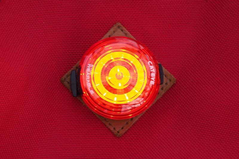 """こちらはウェアラブルライトにもテールライトにもなる「SYNC WEARABLE」(<a href=""""https://www.cateye.com/jp/products/safety_lights/SL-NW100/"""" class=""""strong bn"""" target=""""_blank"""">公式ページ</a>)。曇天下での点灯イメージです。ライトのクリップを使い、バックパック上部のストラップ通しに装着。テールライトSYNC KINETICほどではありませんが、これも目立つ赤色ライトです。なお、SYNC KINETICのキネティックモード発光と連動させ、減速時に赤く明るく光らせることができます。"""