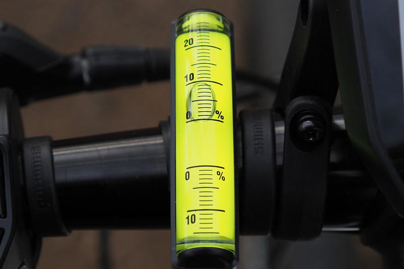 自転車のハンドルにセットした様子。平らな場所で、泡が0%の位置にくる角度で固定します。右写真は約10%の勾配であることを示しています。