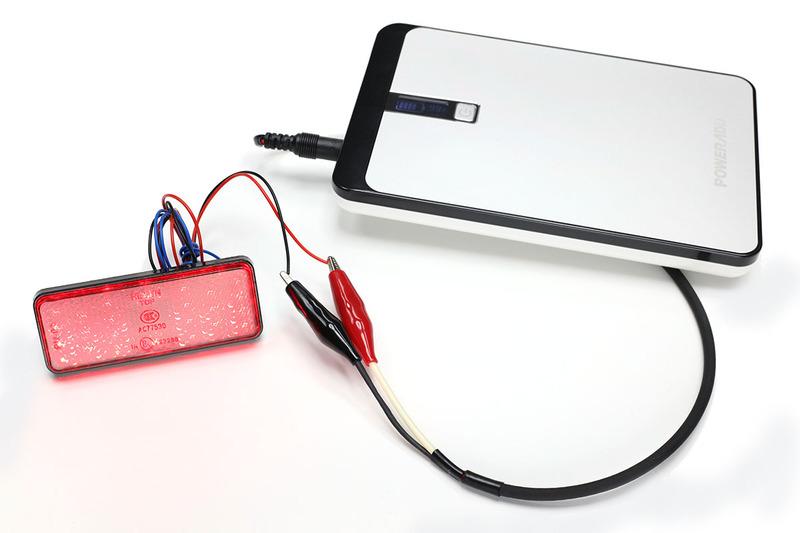 バッテリーのDCジャックから12Vを取り出せるケーブルを作ってみました。先端はワニ口(わにくち)クリップで、これを12V対応モジュールにつないでテストなどします。赤く光っているのは12V対応のテールランプで、12Vの電圧をかけるだけで点灯します。……でも不意にワニ口クリップの先端がショートしたら激ヤバな予感。使用には非常に気を使います。