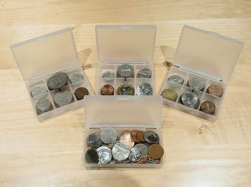いろいろな国の硬貨が大量。最初は国・種類ごとに整理していたが、そのうち面倒になって手前のケースのような状況に