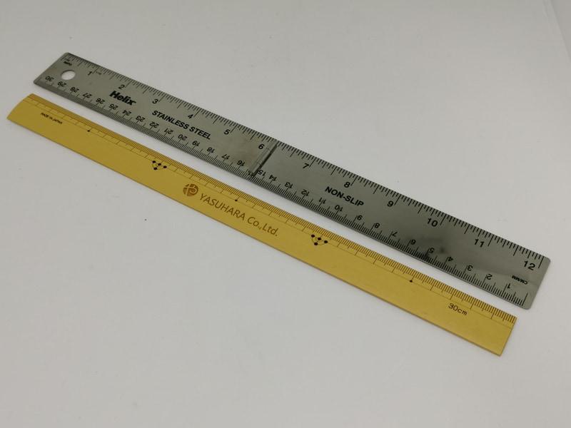 """""""ものさし""""の色彩が濃い日本の伝統的な30cm定規(手前)と今回の折り畳み30cm定規を並べて観たところ、折り畳み30㎝定規の方が多少長さが長い"""