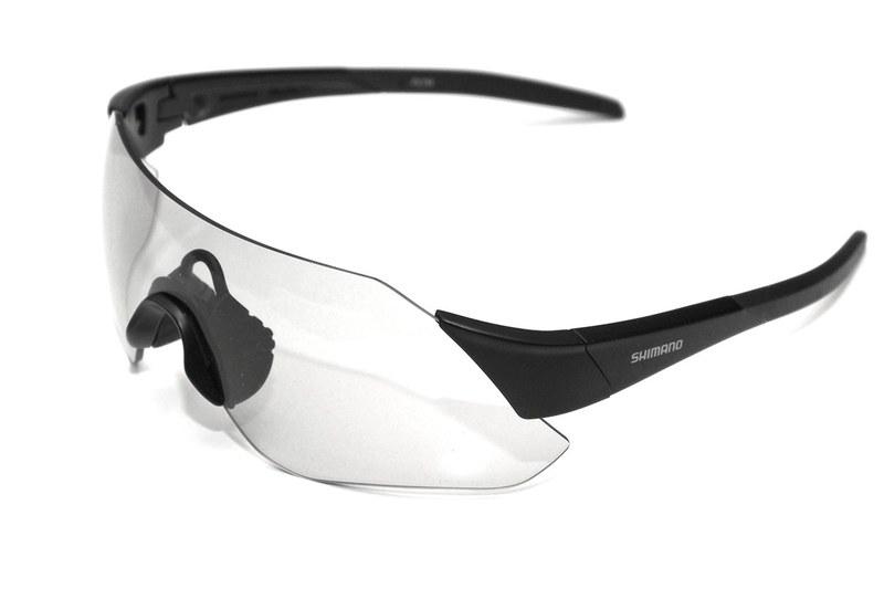サイクリングにはアイウェア(サングラスなど)が必須。風やホコリや紫外線から目を守ってくれるから……ですが、逆にアイウェア無しのサイクリングって苦行じゃない? と思う筆者がお気に入りの「調光レンズ採用サングラス」を紹介。写真はシマノ「CE-ARLT1-PH」という調光サングラスです。紫外線が当たると黒くなり、日陰などでは透明になる。すごーく便利! サイコー! という話を書いています。右は調光サングラスのレンズの一部を黒いテープで覆って紫外線LEDライトの光を照射た様子。意外なほど暗い色に変化します。