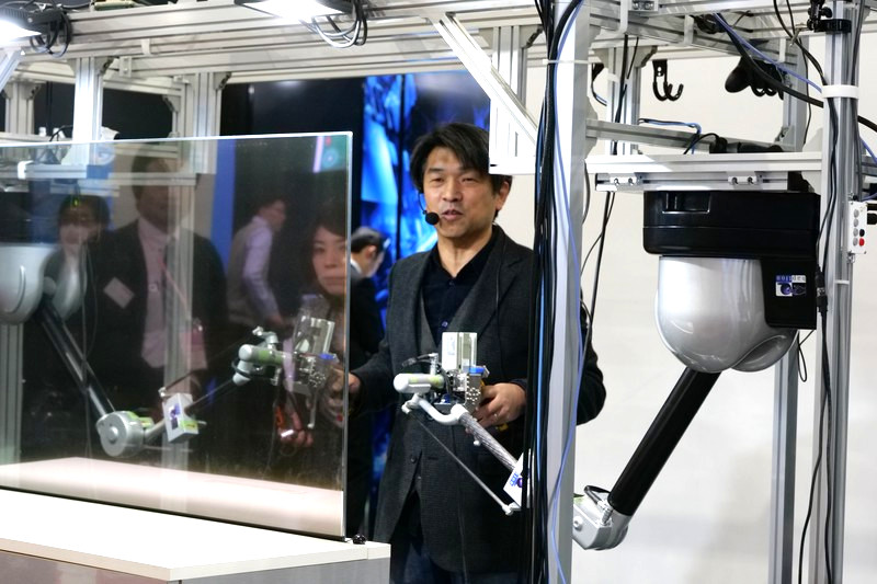 両手にコントローラーを握って操作する。手前の透明の板は半透過ディスプレイで、ロボットからのカメラ映像が表示されている