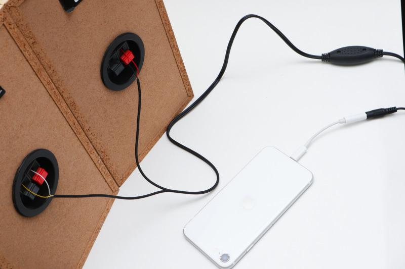 左右のスピーカーに接続、入力としてアダプターを付けたiPhone。電源は適当なUSB充電器を使えば大丈夫だ