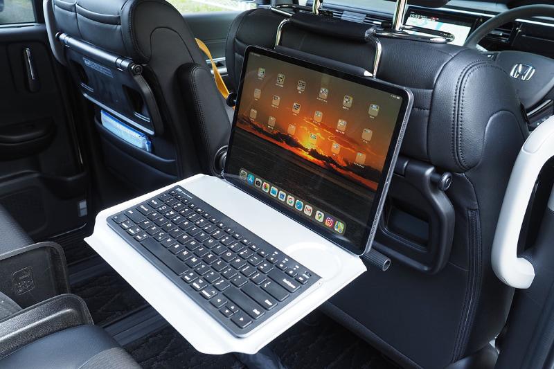 こちらは12.9インチiPad Proを乗せたの図。後部座席が簡易オフィスに早変わりって感じ。