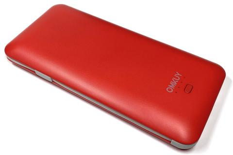"""<a href=""""https://www.amazon.co.jp/gp/product/B07TFSLYKP/"""" class=""""strong bn"""" target=""""_blank"""">Amazonで購入したOMKUYブランドのモバイルバッテリー</a>。容量10000mAhで3880円だった。質量は約256gで、サイズは長辺160×短辺75×厚さ14mm。携帯しやすいサイズである。カラーは赤以外にも白や黒、それからブルーもあるようだ。"""
