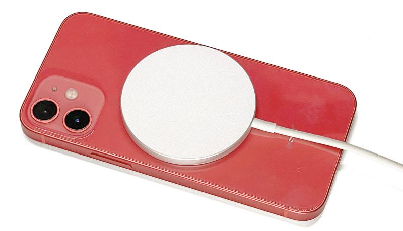 MagSafe充電器をiPhone 12 mini背面にセットしてQi充電している様子。MagSafe充電器は、磁力により端末背面の最適な位置に自動吸着され、端末側と充電器側のコイルが正しい位置関係となり、最適な状態で充電される。