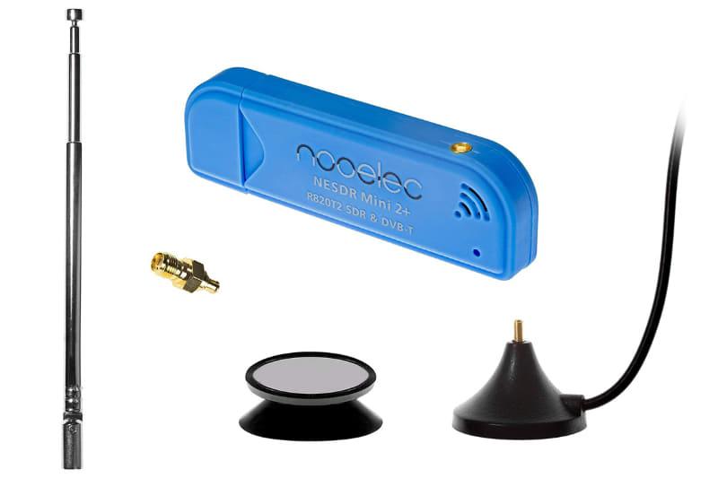 Amazonで売られていたアンテナなどが付属するNooelec「NESDR Mini 2」。左がロッドアンテナで、右下のアンテナ台座(マグネット付き)にねじ込んで使う。このアンテナ台座から伸びるケーブル先端にはMCXプラグがありSDRドングルに直接接続できる。下中央は吸盤付きの台座で、アンテナ台座(マグネット付き)を安定的に吸着できる。中央上がSDRドングル本体。その手前の金色のものはSMA→MCX変換プラグで、外部アンテナからの信号をSDRドングルに送るために使える。