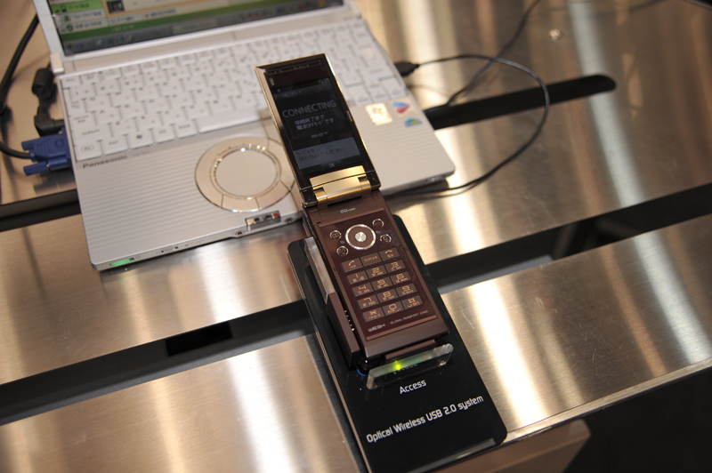 こちらはUSB2.0をGiga-IRでワイヤレス化するデモ。スタンドに緑色のランプが点灯し、携帯電話からはUSBケーブルが接続されたように認識されている