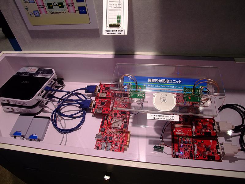 デモは、地デジ映像を2台のパソコンで伝送し、光ファイバーを経由して2台のディスプレイに配信するというもの