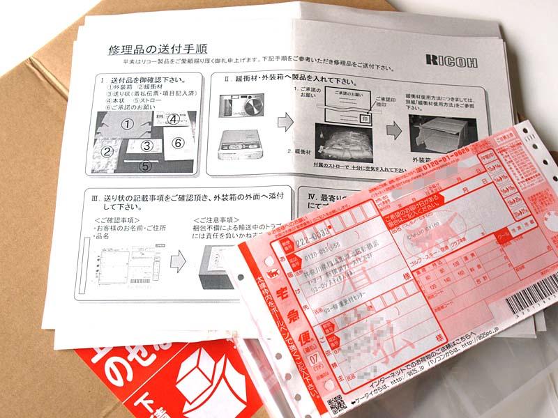 リコーから送られてきたサポートキット一式。段ボール箱、着払い伝票、梱包材、送付手順説明書等だ。着払い伝票には、こちらの住所氏名等およびGX100の製造番号まで印字されていた。何かを記入する必要はナシ。