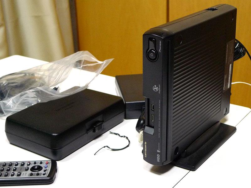 ネット経由でのバージョンアップは、ナビの中核となるHDD(ブレインユニット)と、ナビ付属のリビングキット、テレビ、ブロードバンド回線があればOK。写真はリビングキットだ。