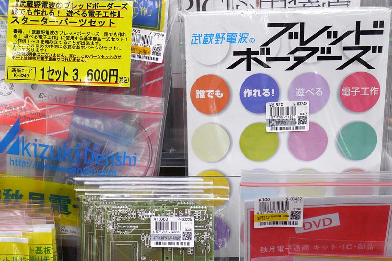 """秋月電子通商店頭に並べられた書籍「武蔵野電波のブレッドボーダーズ 誰でも作れる! 遊べる電子工作」と、書籍に対応した部品キット。両方とも<a href=""""http://akizukidenshi.com/catalog/g/gS-03248/"""">Web通販で購入可能</a>なんでゼヒ!!"""