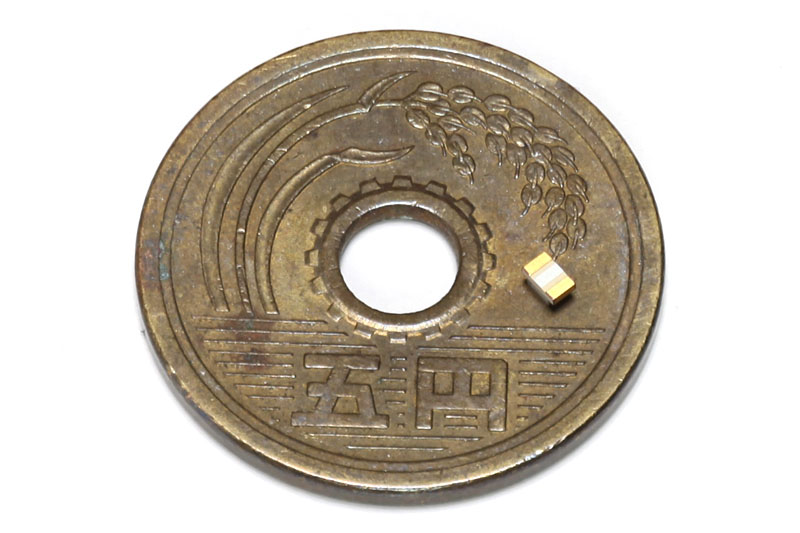 2012サイズのチップ部品を5円玉に乗せたところ。クシャミ一発で消失確実のサイズですな。これを基板にハンダ付けする