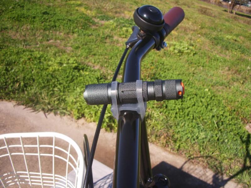 自転車のハンドルに小型の懐中電灯を取り付けてみる。意外なほど安定性が高い