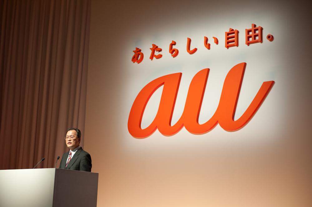 KDDI 代表取締役社長の田中孝司氏と、発表会の途中で披露されたauの新しいロゴ