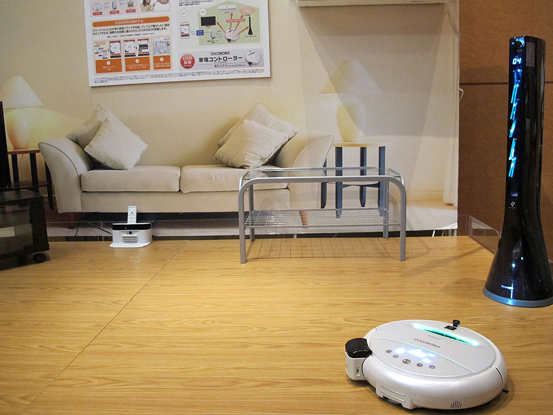 リビングを模してデモンストレーション。スマートフォンで遠隔からCOCOROBOを操作し、宅内の空調を入れた