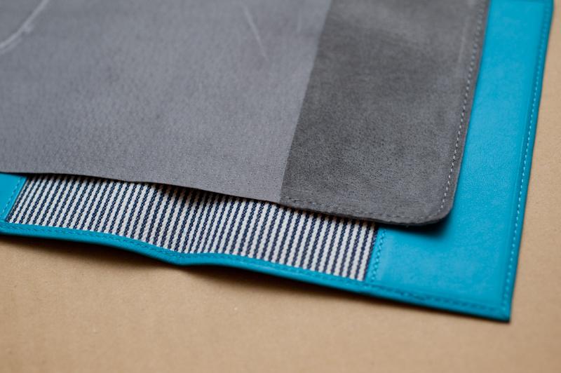 一般的な革製カバー(手前・水色)と比較。縁を縫わず、薄さを追求している