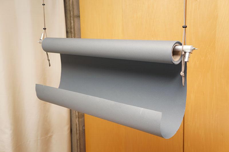 天井の取っ掛かりから写真撮影用の背景紙(をセットするパイプ)を吊した状態。紐のストッパーを利用すれば、背景紙の高さも手軽に調節できるのだ。