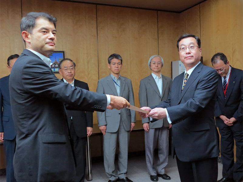 認定書を手渡す柴山副大臣(左)と受け取るUQ野坂社長(右)、野坂氏の後方に田中氏