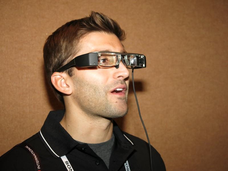 メガネの上にクリアレンズのMoverioを装着しているエプソン説明担当者