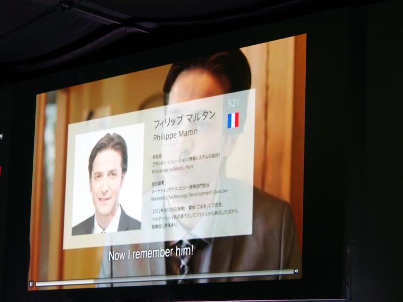 外国人との会食の場で、会話の内容をスマートフォンでリアルタイムに翻訳しつつ、相手の情報がメガネ型デバイスに表示されるという世界が示された