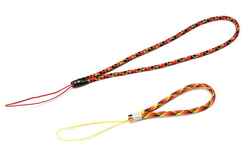 自作したケータイ用ストラップ。パラコードなどの化繊紐と少々の樹脂部品を使って作った。長さも紐の色や柄も自由自在に作れるのが愉快。右の写真は化繊紐のみで作ったもの。金属部品を使わないので端末を傷付けにくい