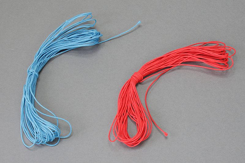 左は松葉紐各種。コシのある化繊紐で、カラーもいろいろ。0.5mmくらいの太さのものが、ケータイ用ストラップに多用されているものだ。右は幅5mmの平紐。これらを樹脂部品で組み合わせてストラップを作ってみよう
