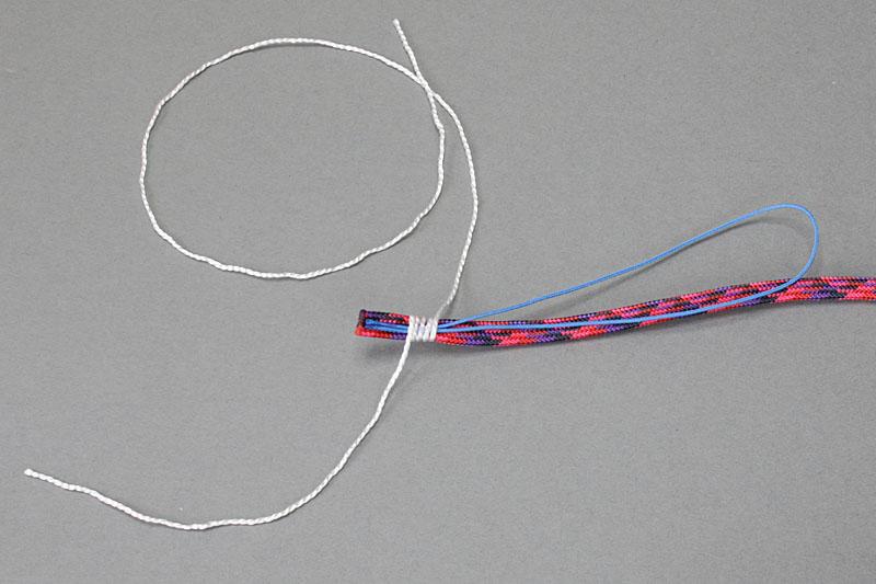まず写真のように、パラコードへ松葉紐を接着する。接着は仮止め程度で十分。次にパラコード芯紐で松葉紐を固定する。芯紐を3回くらい巻いたら瞬間接着剤で仮止めする