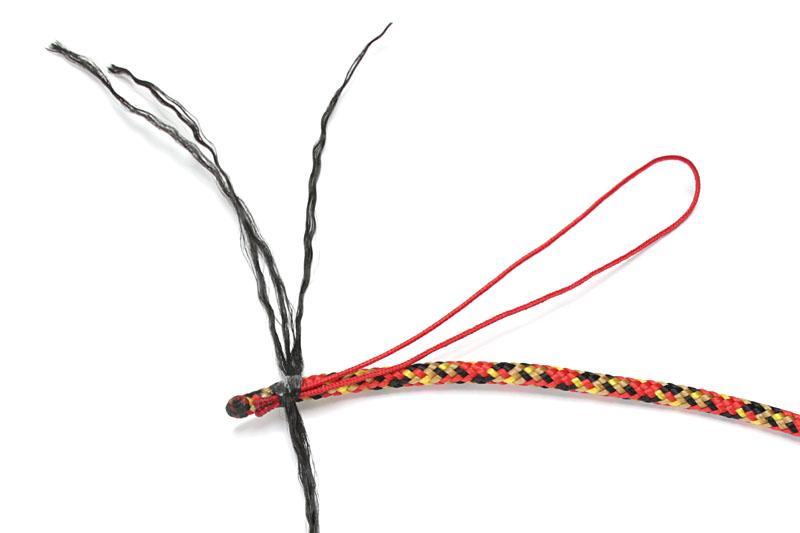 ではストラップ作成。バンナイズ紐に松葉紐をセットし、バンナイズ紐の芯紐で巻き止める。ココでは(撮影の都合上)瞬間接着剤で仮止めしているが、ライターで軽くあぶれば溶着できる。接着剤を使わずに作業を進めていけて手軽だ
