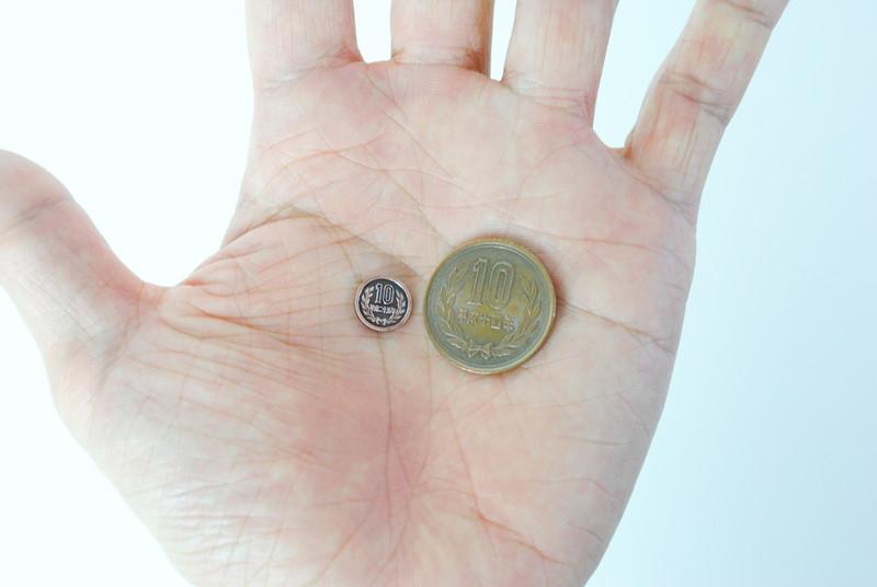 本物の硬貨と比較。ホームボタンに合わせた小さめのサイズなのに、なかなか再現度は高い