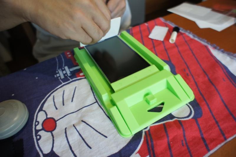スクイーザーで気泡を抜きつつ液晶保護フィルムをスマホに貼付けていく
