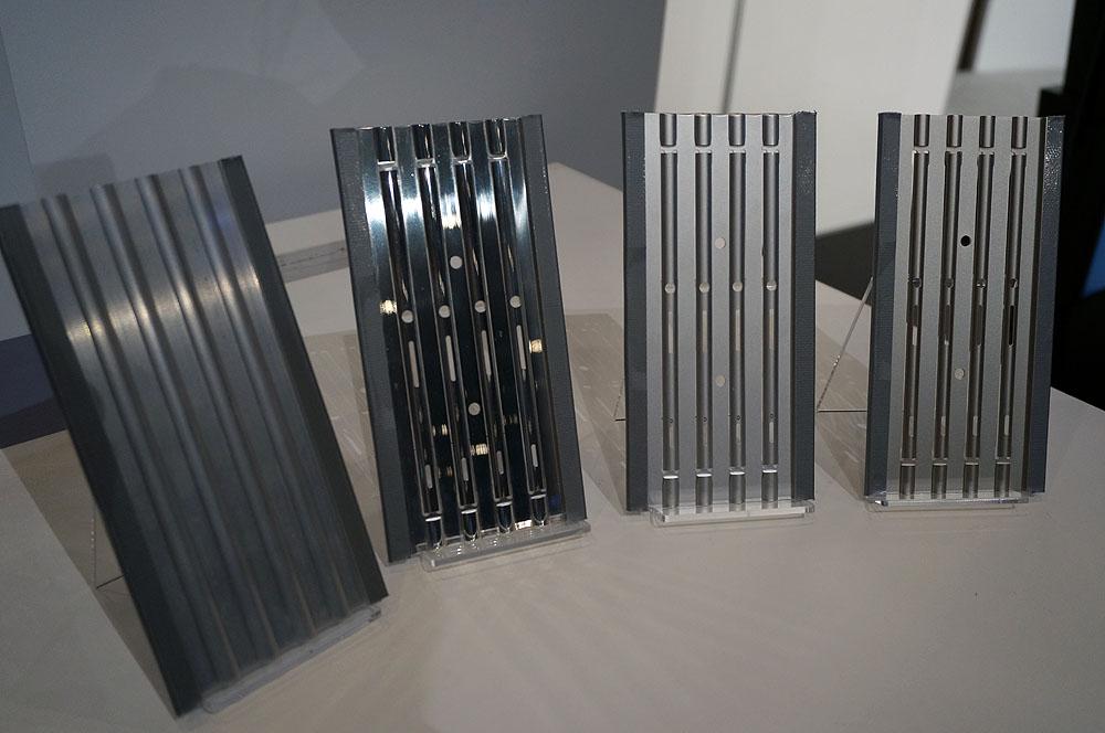 側面のアルミフレームを4段階の製造工程別に解説。一番左が押し出しで原形を作った状態。右に行くに従って、磨き、砂での磨き、アルマイト加工となっている