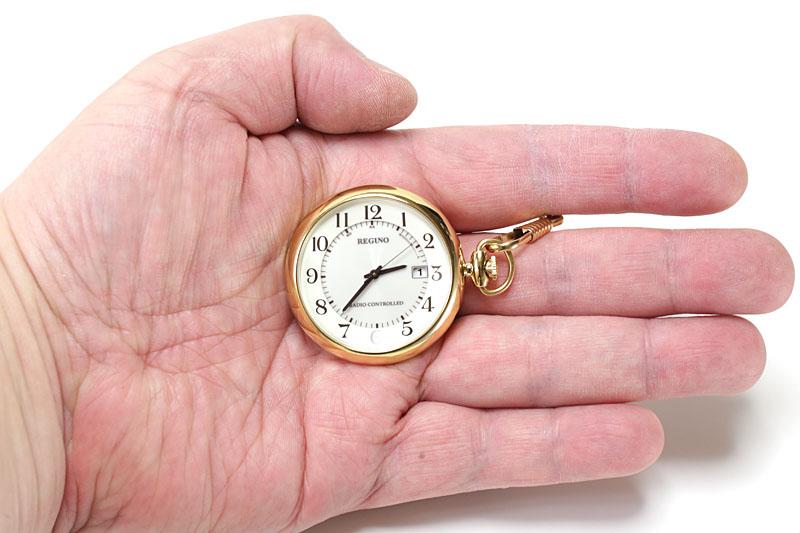 右にリュウズおよびチェーンがあるので、指の間にチェーンを通してポケットなどから出せば、そのまま違和感なく文字盤を見られます。リュウズが上にある懐中時計の場合、人差し指と親指の間に鎖をかければ、違和感なく文字盤を見られます。