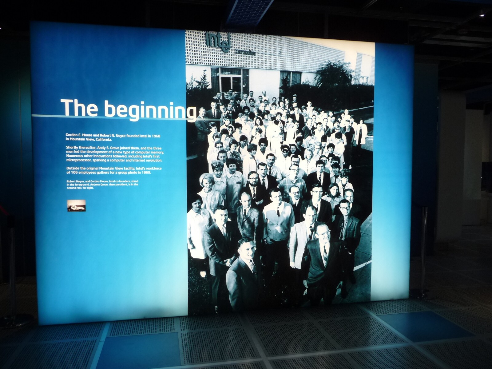 Intelの創業地であるマウンテンビューの本社前に従業員が集まって撮影された写真(1969年)のパネル。最前列の左がロバート・ノイス(初代の社長兼CEO(最高経営責任者))、右がゴードン・ムーア。社屋には1969年にデザインされた有名なロゴマーク(ドロップドイー(dropped-e)と呼ばれる、「e」の文字だけが下がっているロゴ)が見て取れる