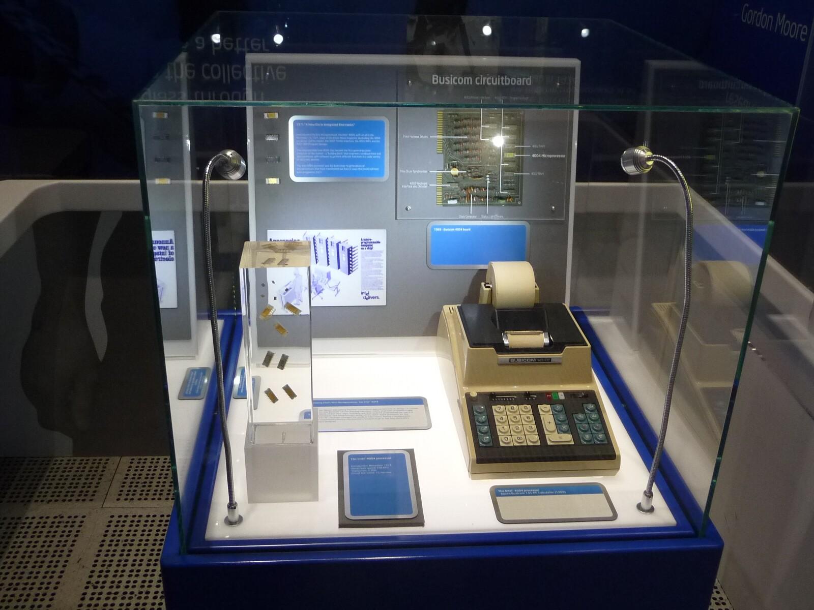 世界初のマイクロプロセッサ「4004」の展示棚。左手前が、「4004」を埋め込んだ樹脂のオブジェ。右手前が、「4004」の開発目的である、プリンタ付きの電子式卓上計算器(desktop calculator)「141-PF」の実物。「141-PF」は、日本の計算器販売会社「ビジコン」が開発した。右奥のプリント基板は、「141-PF」のメインボード。左奥のパッケージ群は、「141-PF」のためにビジコンとIntelが共同開発した「4004」を含む4種類の半導体集積回路。その下にあるのが、電子業界誌「Electronics News」の1971年11月15日号に掲載された、「4004」を含めたチップセットの広告原稿のコピー。2017年6月某日に「インテルミュージアム」で筆者が撮影(以下同じ)