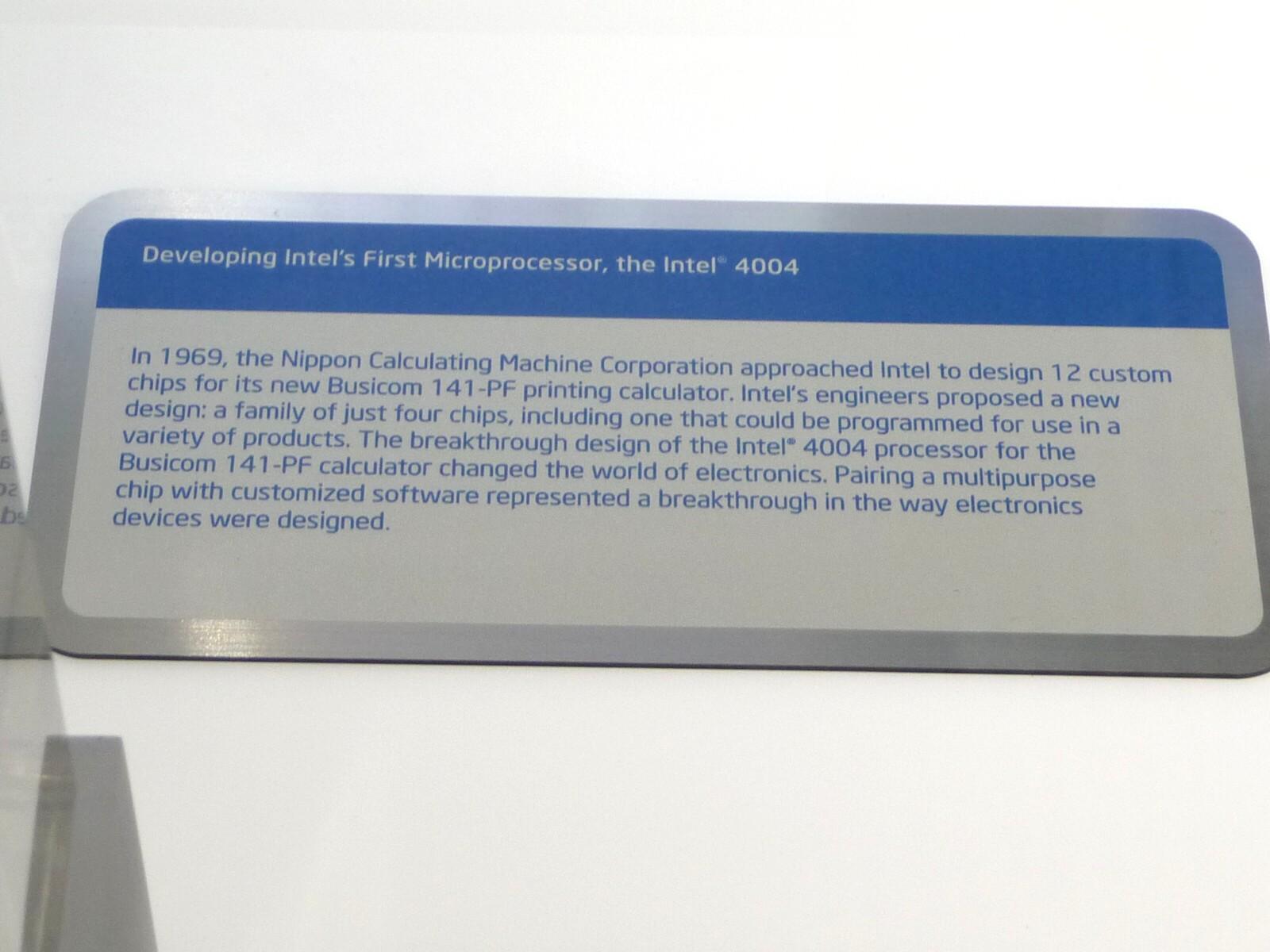 """世界初のマイクロプロセッサ「4004」の展示棚に置かれた、「4004」の開発経緯に関する説明パネル。なお日本のビジコンが提案したカスタムチップを12種類と説明パネルで記述しているのは誤りで、ビジコンの技術者である嶋正利氏(当時)は<a href=""""http://itpro.nikkeibp.co.jp/article/Watcher/20070418/268753/"""" class=""""n"""" target=""""_blank"""">8種類のカスタムチップを合計で12個使うと述べており</a>、Intelは12個を12種類と誤って理解したものと思われる"""