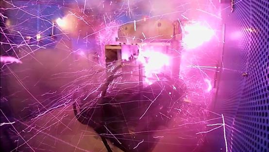 磁場発生瞬後の様子。強磁場発生時には強力なマクスウェル応力がともない、1,000テスラで4×1011N/平方m(400万気圧)に達し、その瞬後に爆発が発生する。そのため装置全体を防護箱(青い壁面)で覆い、磁場発生装置の制御と計測は離れたシールドルームで行なう