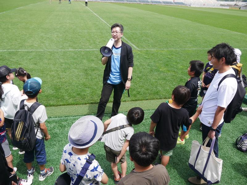 子供たちは、講師を務めたタツナミ・シュウイチ氏とともにフィールドに降りて、スタジアムの様子を見学