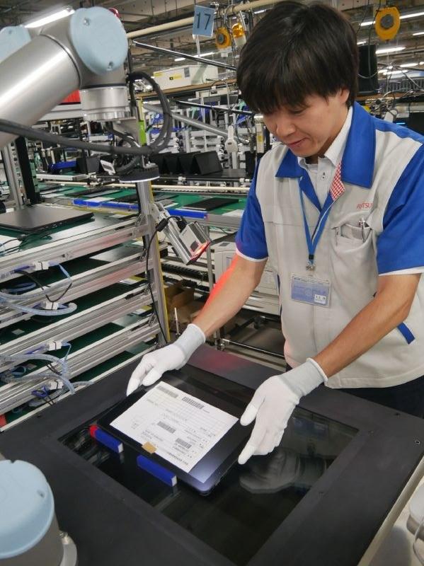 外観検査ロボットにタブレットをセットする様子。外観検査ロボットには安全柵などがない