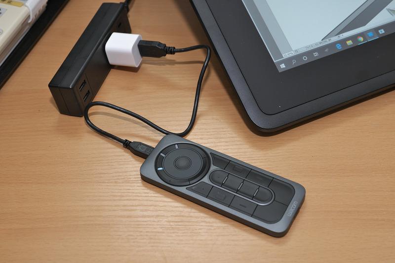 """別売オプションの<a href=""""https://store.wacom.jp/products/detail.php?product_id=2775"""" class=""""n"""" target=""""_blank"""">ExpressKey Remote</a>(直販価格 : 13,824円)はワイヤレス接続なので、充電以外でUSBにつなぐ必要はなし。でも、なんとなくとつぜん切れるのがイヤ、ということで横にUSB給電器を持ってきて使っていたざら先生"""