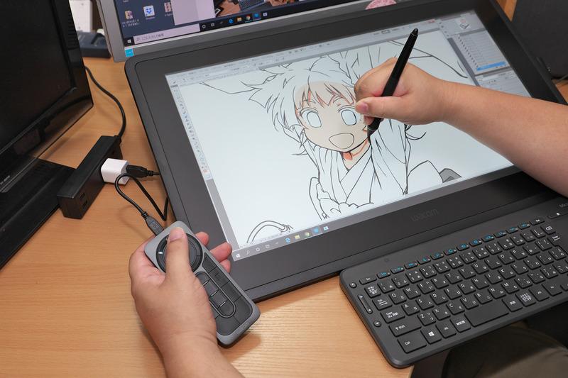 作画風景2。ExpressKey Remoteは机の上に置くのも、本体上に置くのも手首が疲れるので、この持ち方が一番しっくりくる、とのこと。Cintiq Pro 24とは大きさも額縁の太さも違うので、左手の使い方も変わるのかも