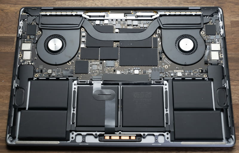 MacBook Pro 16インチモデルの内部。ヒートパイプが左右に走っているが、その真下にGPU(左側)とCPU(右側)が配置されている。ヒートパイプからやや離れた場所にメインメモリやVRAMが実装されているが、各チップには放熱用素材が貼りつけられているため、直接型番などを確認することはできない