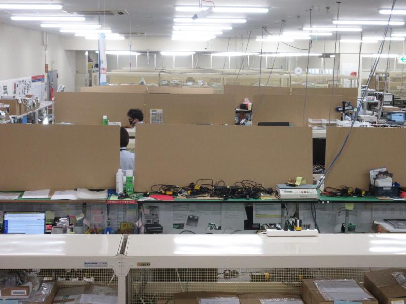新型コロナウイルスの感染防止のために作業台の間をダンボールで区切っている