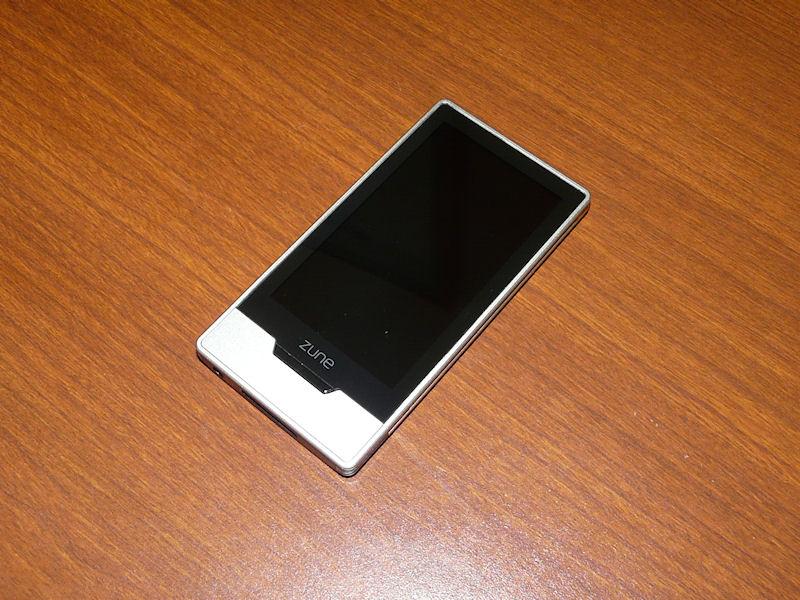 Zune HD本体正面。Zuneのと書かれたすぐしたにトップボタンがある