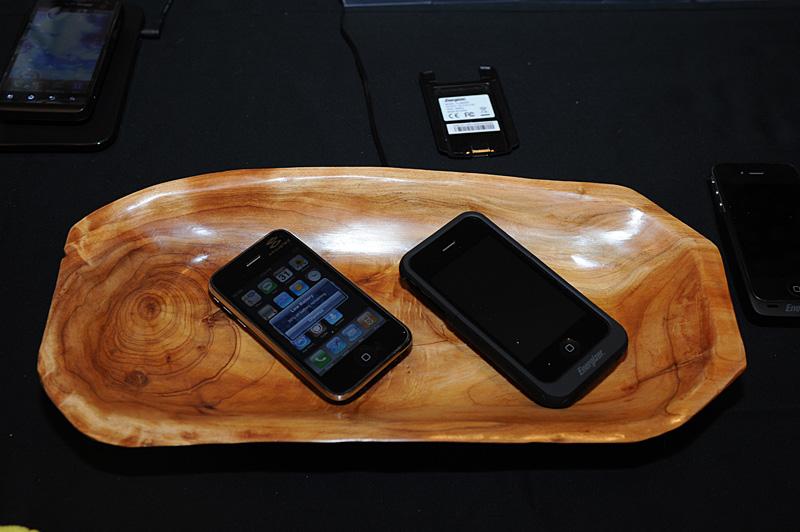 CESに続いて出展されたサンプル。木枠トレイに見えるがワイヤレス充電のチャージャーになっている。iPhone 3G/3GSはプロトタイプの改造品。右のiPhone 4向けジャケットタイプはEnegizerから市販されている