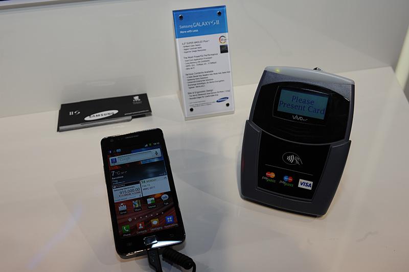 SamsungブースでのNFCデモの様子。リーダーに使われているのは、クレジットカード向けに利用されている非接触の端末機。米国内で対応クレジットカードを使うことで決済が可能。NFC化でそうしたクレジットカード決済機能が携帯端末側に取り込まれる