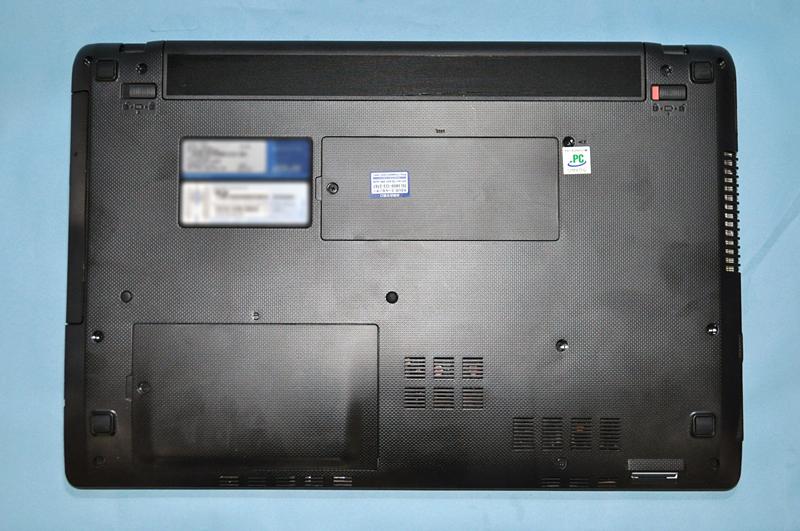 K53TAの背面。中央上部にメモリスロットのカバーが、左下にHDDのカバーがある