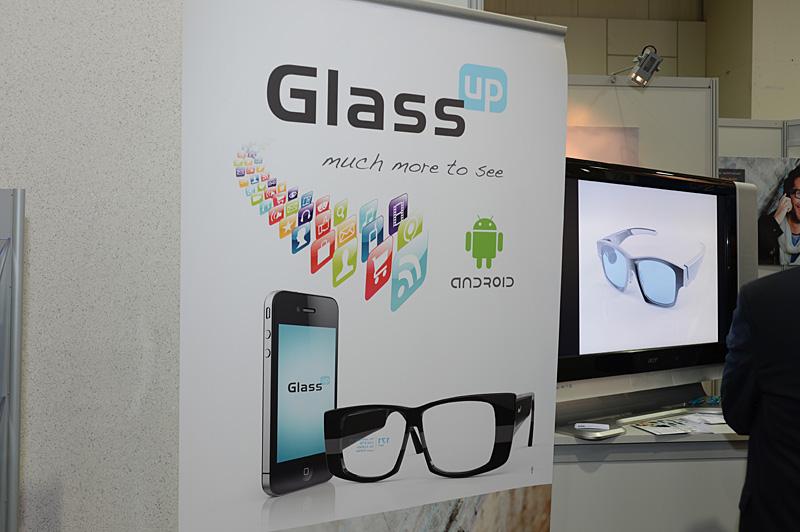 おなじくM31グループがサポートする「GlassUP」。メガネのリム部分のユニットから、レンズ面に映像を投影する。表示は黄色の単色。シースルーで視界を完全に遮ることはない。解像度は320×240ドット。加速度センサー、電子コンパス、ライトセンサー、高度計などの各種センサー類を搭載する。通信機能はBluetooth。Android、iOS、Windows Phoneに対応するサードパーティ向けのSDKも用意される。価格は299ユーロですでにプリオーダーを受け付けており、2013年9月に出荷開始の見通し